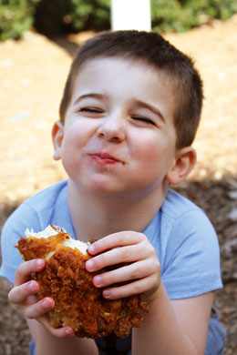 young boy enjoying a piece of fried chicken